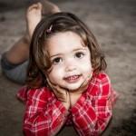 Foto niña tumbada en la arena