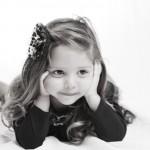 foto niña tumbada con manos en la cara
