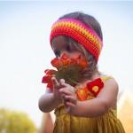 Foto niña oliendo flor